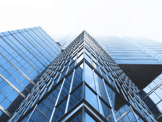 upwards view of skyscraper from sidewalk