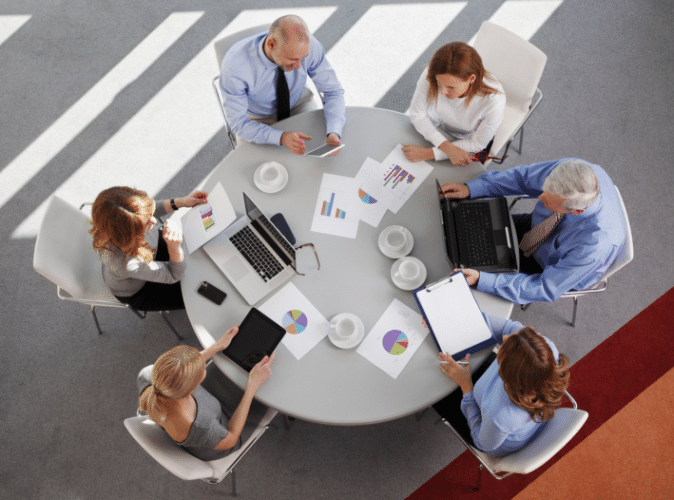 team of 6 business persons working together at a circular table