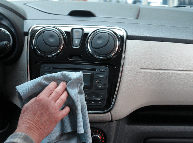person cleaning automobile radio with rag