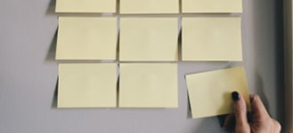 Blank, yellow post-it notes being placed on a wall.