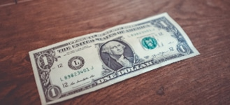 single dollar bill atop wooden table